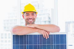 Smiling manual worker with solar panel in office Royalty Free Stock Image