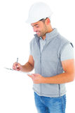 Smiling manual worker writing on clipboard Stock Images