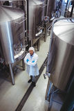 Smiling manufacturer standing at brewery Stock Image