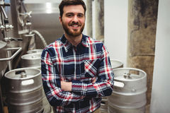 Smiling manufacturer standing in brewery Stock Image