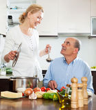 Smiling married mature couple cooking in kitchen Royalty Free Stock Image