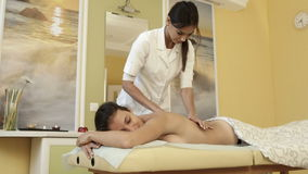 Smiling masseuse doing massage on young woman body in a spa salon stock video