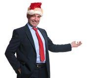 Smiling mature business man in santa claus hat presenting Stock Photo