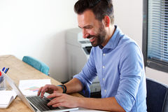 Smiling mature business man working on laptop. Side portrait of smiling mature business man working on laptop at his office desk royalty free stock images