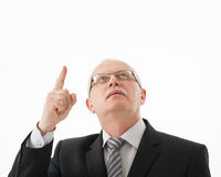Smiling mature businessman looking and indicating up Royalty Free Stock Image