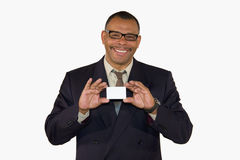 Smiling mature businessman presenting card. A smiling mature African-American businessman showing a business card with copy space, isolated on white background Royalty Free Stock Photo
