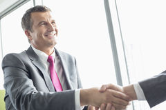 Smiling mature businessman shaking hands with partner in office Royalty Free Stock Photo