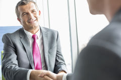 Smiling mature businessman shaking hands with partner in office Royalty Free Stock Image