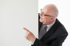 Smiling mature businessman showing something on white board Stock Photos