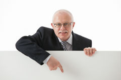 Smiling mature businessman showing something on white board Royalty Free Stock Photography
