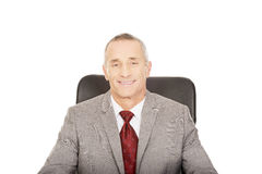 Smiling mature businessman sitting on armchair Stock Photography