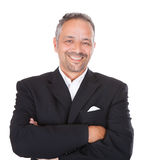 Smiling mature businessman standing arms crossed Royalty Free Stock Photos