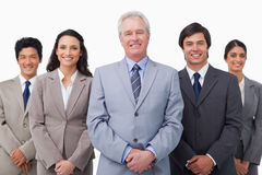 Smiling mature businessman standing with team Stock Photos