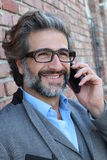 Smiling mature businessman talking on the cell phone stock image