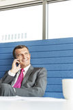 Smiling mature businessman talking on cell phone in office Royalty Free Stock Photo