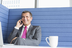 Smiling mature businessman talking on cell phone in office Royalty Free Stock Images