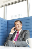 Smiling mature businessman talking on cell phone in office Stock Photography