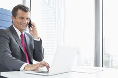 Smiling mature businessman talking on cell phone while using laptop in office Stock Photos
