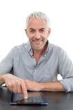 Smiling mature businessman using digital tablet at desk Stock Photos