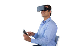 Smiling mature businessman wearing vr glasses while using digital tablet Royalty Free Stock Image