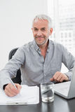 Smiling mature businessman writing notes while using laptop Royalty Free Stock Images