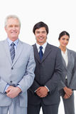Smiling mature businessman with young employees. Against a white background Royalty Free Stock Images