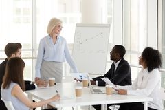 Smiling mature businesswoman hold business meeting with young em. Smiling middle aged businesswoman stand holding business meeting with young colleagues stock photo