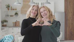 Smiling mature Caucasian women standing in luxurious kitchen and falding fingers into heart shape. Rich senior female
