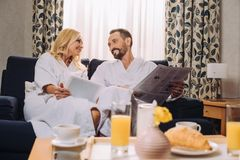 smiling mature couple in bathrobes holding newspaper and digital tablet while having breakfast in hotel royalty free stock photos
