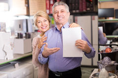 Smiling mature couple buying on credit agreement for home applia Stock Photo