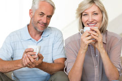 Smiling mature couple with coffee cups sitting on sofa Royalty Free Stock Photo
