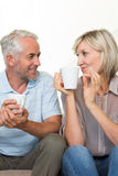 Smiling mature couple with coffee cups sitting on sofa Royalty Free Stock Photos