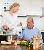 Smiling mature couple cooking together in kitchen Stock Photography