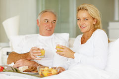 Smiling mature couple eating breakfast in bed Royalty Free Stock Image