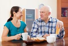Smiling mature couple having tea stock photo