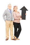 Smiling mature couple holding a big black arrow pointing up Royalty Free Stock Photography