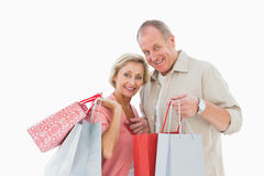 Smiling mature couple holding shopping bags Royalty Free Stock Images