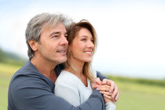 Smiling mature couple looking towards future. Portrait of smiling middle-aged couple in countryside stock images