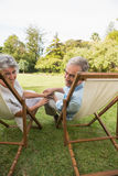 Smiling mature couple lying on sun loungers Stock Image