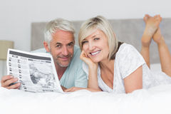 Smiling mature couple reading newspaper in bed Royalty Free Stock Photo