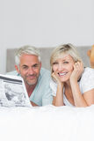 Smiling mature couple reading newspaper in bed Stock Photo