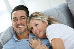 Smiling mature couple relaxing on sofa Stock Image