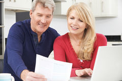 Smiling Mature Couple Reviewing Domestic Finances Stock Photography
