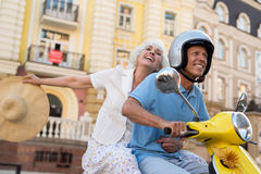Smiling mature couple rides scooter. Stock Images