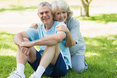 Smiling mature couple sitting on grass at park Royalty Free Stock Photo