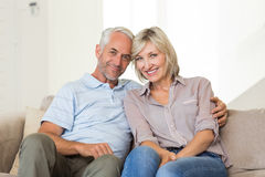 Smiling mature couple sitting on sofa with arm around Stock Photo