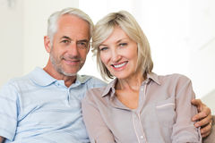 Smiling mature couple sitting on sofa with arm around Stock Image