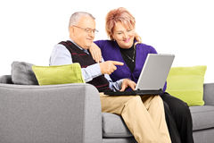 Smiling mature couple sitting on a sofa and looking at laptop Stock Image