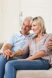 Smiling mature couple sitting on sofa Stock Image