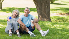 Smiling mature couple sitting with water bottles at park Royalty Free Stock Photos